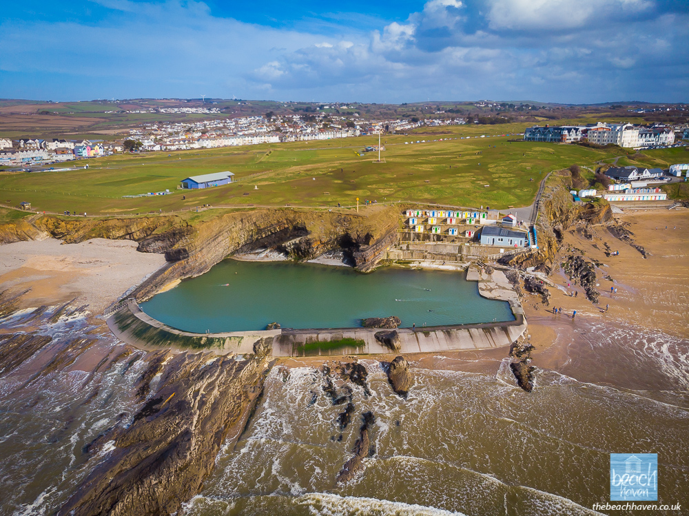 Bude's fabulous open-air sea pool with some hardy souls enjoying in the chilly March water! Summerleaze Downs and the cricket pitch are immediately behind and show how much lovely green space we have in Bude.