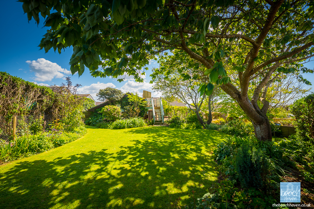 The tree-lined enclosed garden at the Beach Haven dog-friendly holiday cottage at Bude, Cornwall