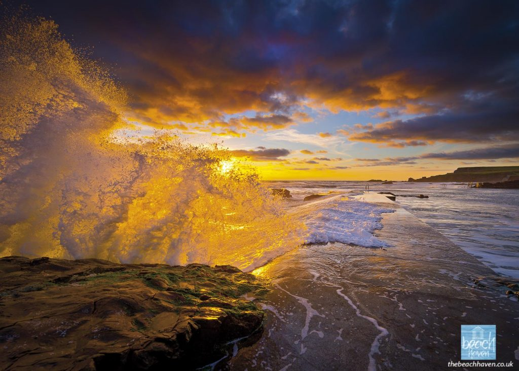 Splashing wave at the Sea Pool at sunset